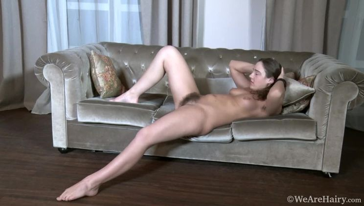 Dominique strips naked on her brown couch