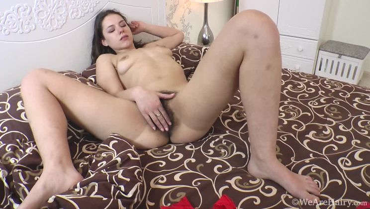 Canella lays across her bed stroking her sexy body